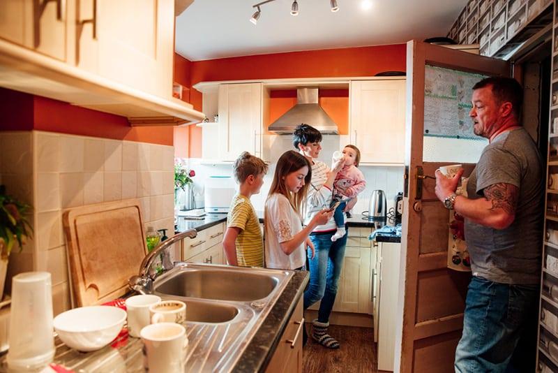 Eine ganze Familie ist in der Küche ihres Hauses beschäftigt
