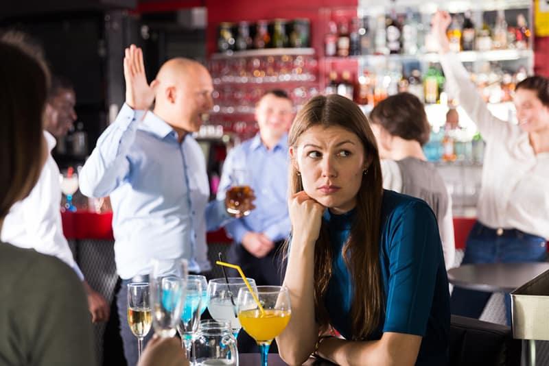 Eine gelangweilte Frau, die am Tisch unter tanzenden Kollegen auf einer Firmenfeier sitzt