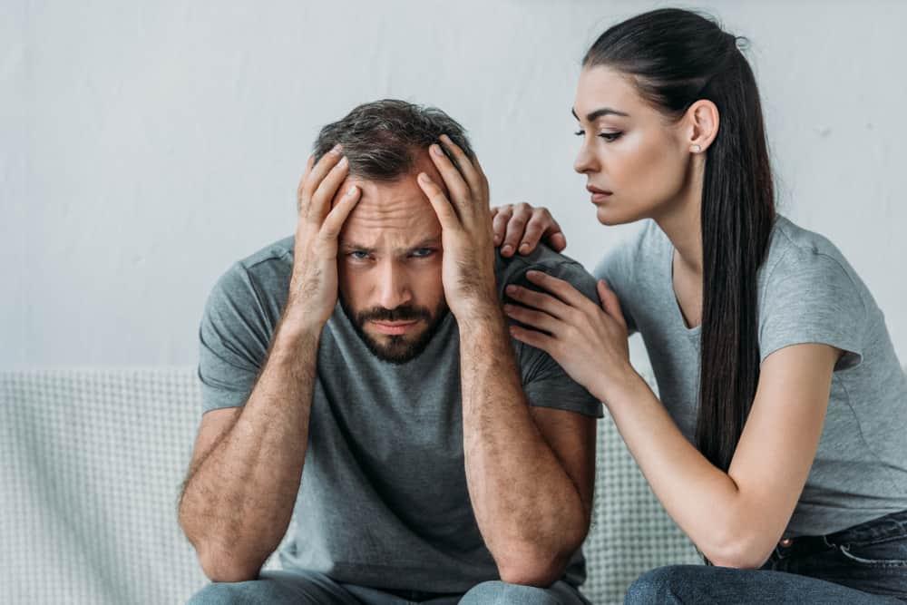 Eine junge Frau auf der Couch tröstet einen depressiven Mann