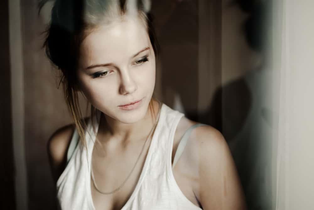Eine junge Frau in einem Unterhemd steht und denkt nach