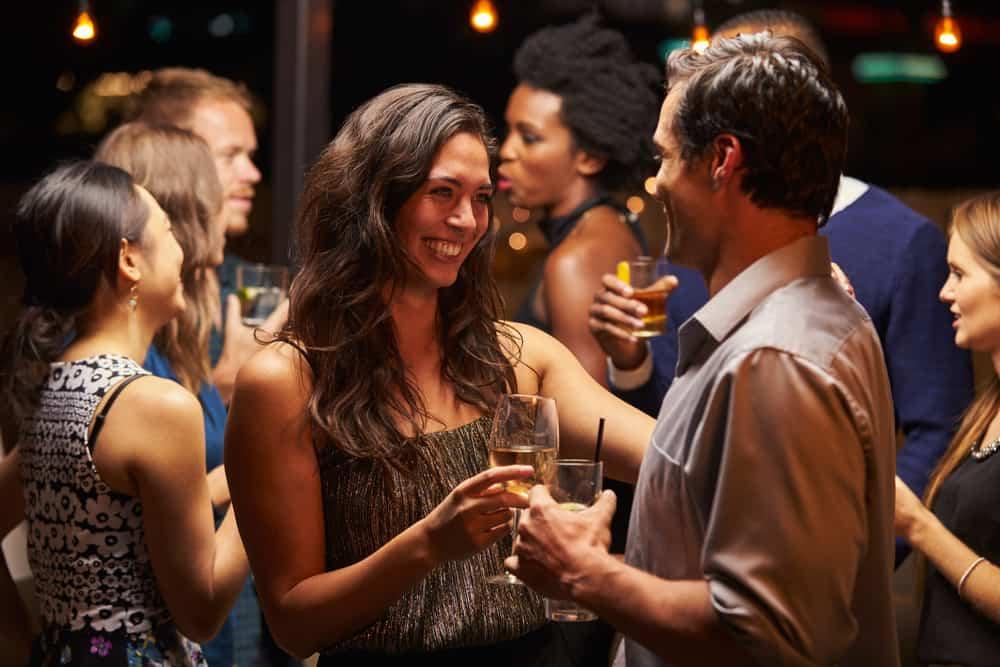 Eine lächelnde Frau auf einer Party tanzt mit einem Mann und trinkt Wein