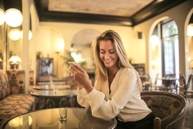 Eine lächelnde Frau trinkt in einem Café und benutzt ein Handy