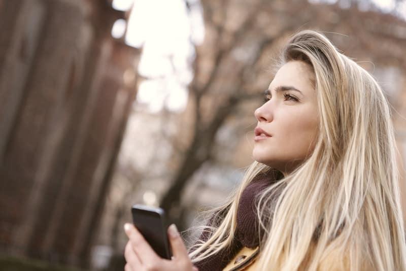 Eine nachdenkliche Blondine steht mit einem Telefon in der Hand im Wald
