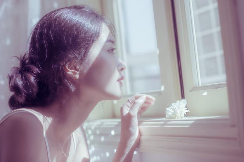 Eine nachdenkliche Chinesin sitzt und schaut aus dem Fenster