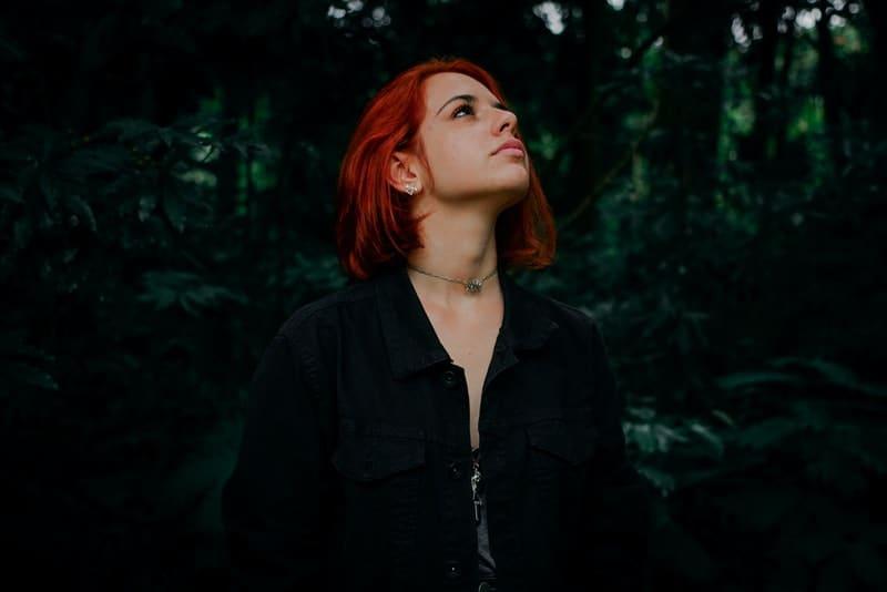 Eine rothaarige Frau steht im Wald