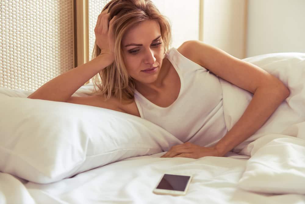 Eine schöne Blondine liegt auf dem Bett neben einem Handy, das sie traurig ansieht