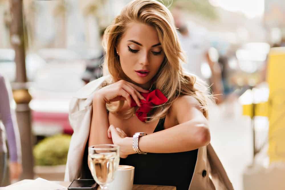 Eine schöne Blondine sitzt in einem Café und wartet ungeduldig auf jemanden