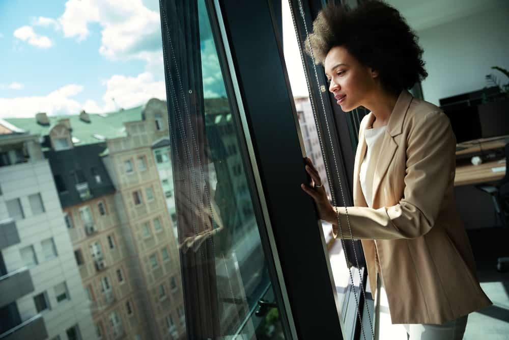 Eine schöne schwarze Frau schaut aus dem Bürofenster
