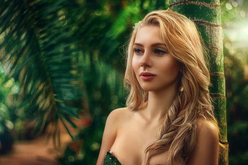 Eine schöne traurige Blondine steht unter einer Palme