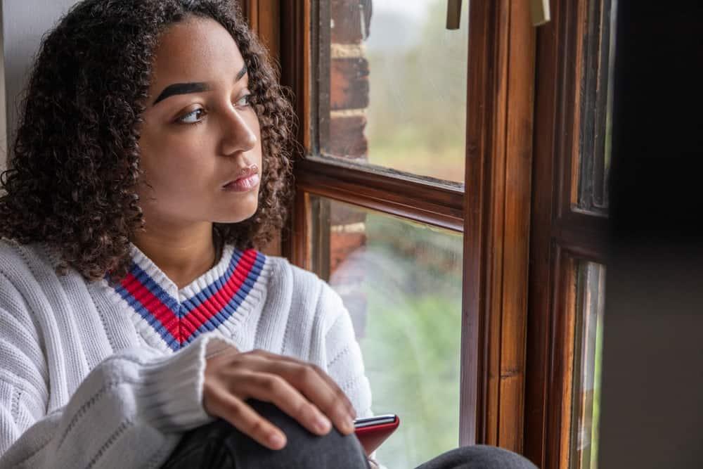 Eine schöne traurige schwarze Frau mit einem Handy in der Hand sitzt am Fenster