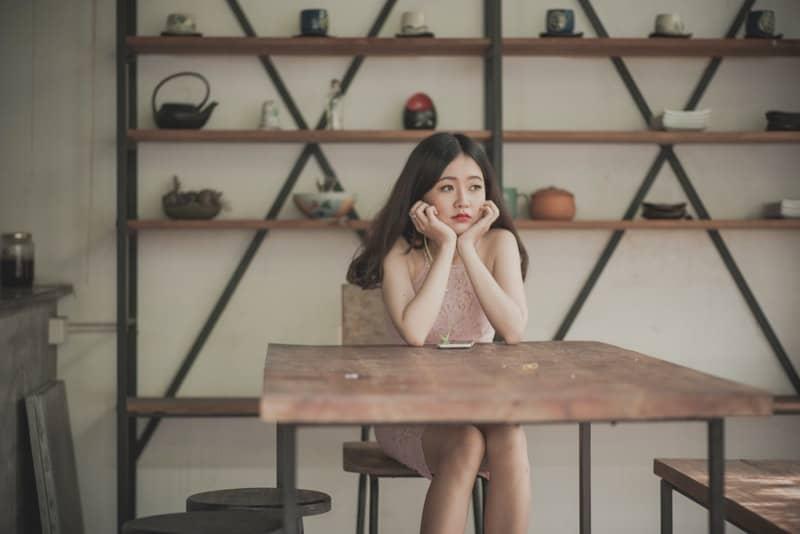 Eine traurige Chinesin sitzt an einem Tisch