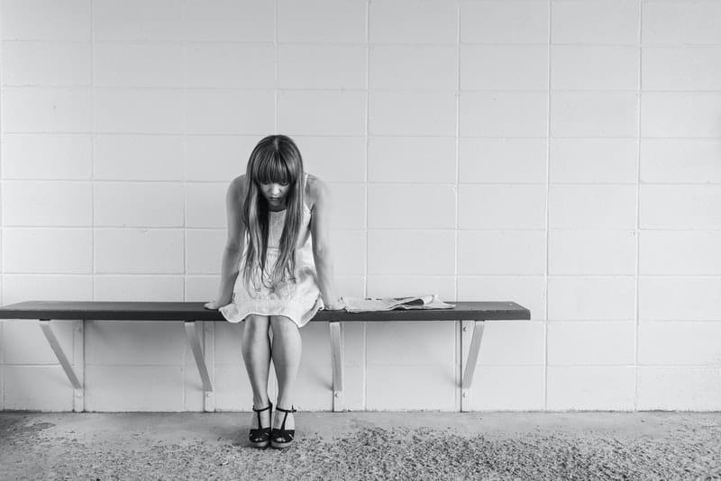 Eine traurige Frau in einem weißen Kleid sitzt auf einer Bank