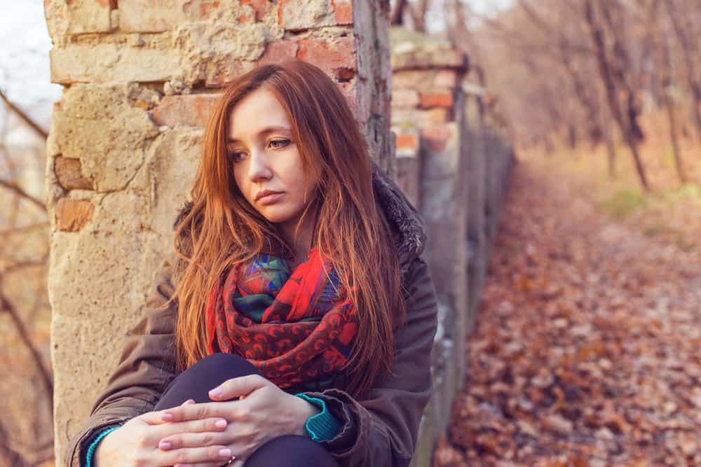 Eine traurige Frau sitzt draußen auf dem Boden und lehnt sich an eine alte Wand