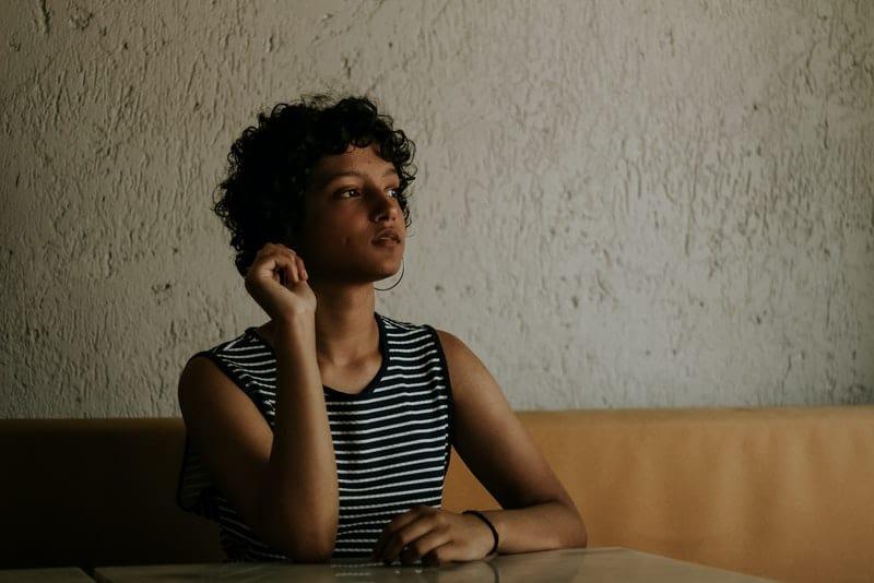 Eine traurige kurzhaarige Frau in einem Matrosenhemd sitzt an einem Tisch und denkt nach