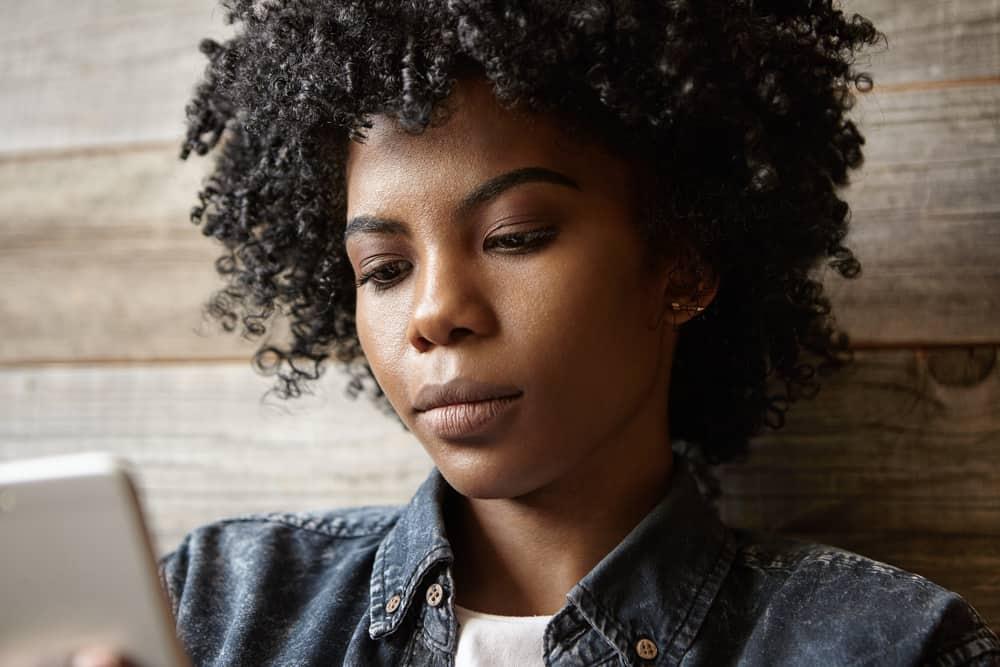 Eine traurige schwarze Frau benutzt ein Handy