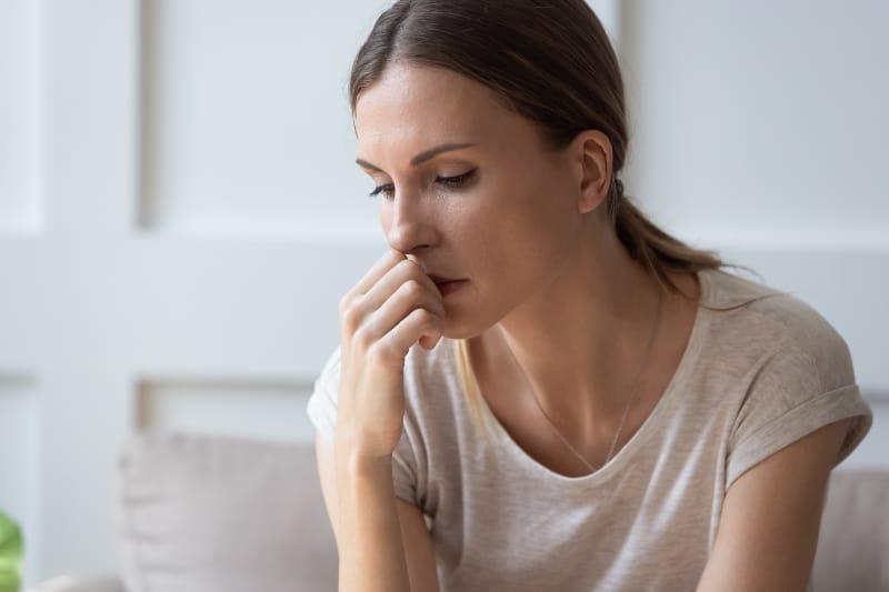 Eine unsichere Frau sitzt und denkt nach