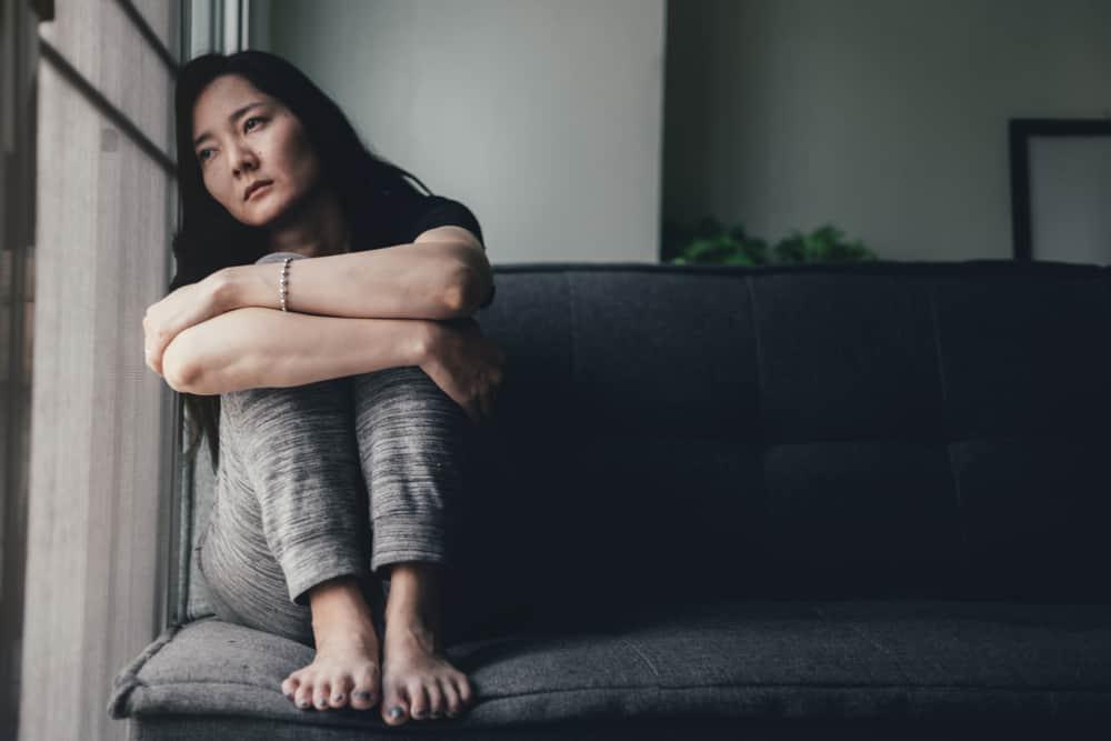 Eine verängstigte Chinesin sitzt auf der Couch am Fenster