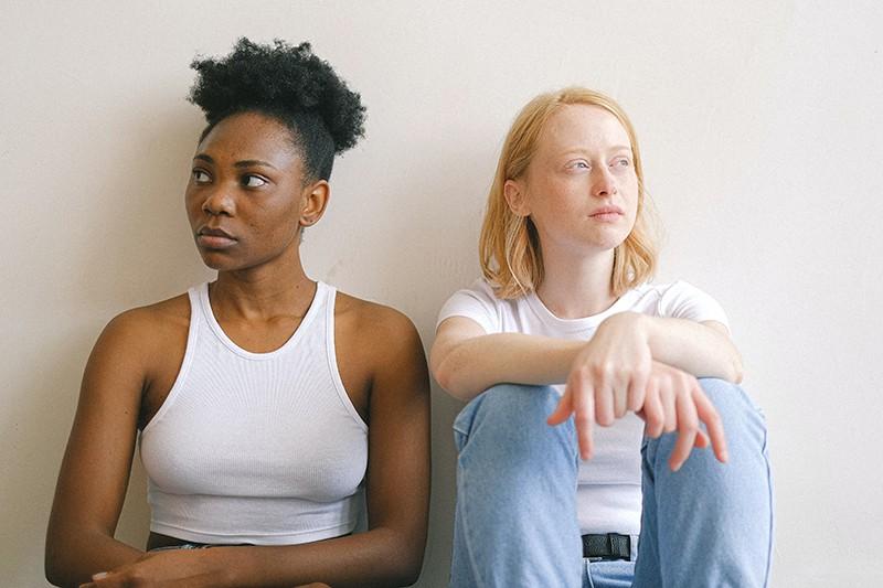 Eine verärgerte Frau mit verschränkten Armen sitzt neben ihrem Partner und lehnt sich an die Wand