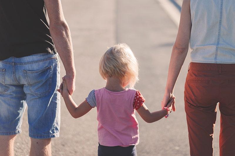 Eltern halten Hände mit ihrem Kind, während sie auf der Straße gehen