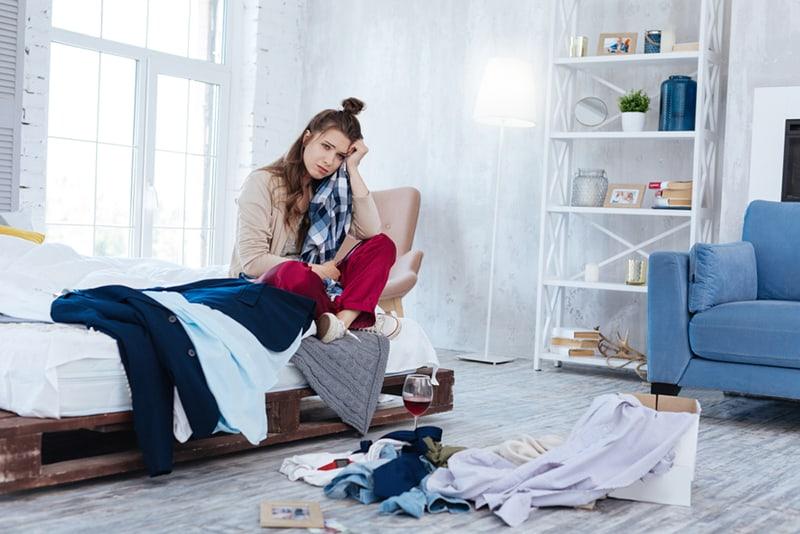 Emotional depressive Frau, die alle Kleider eines Ex-Freundes wirft und auf der Couch sitzt