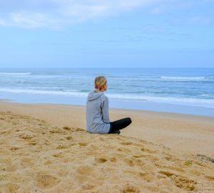 Eine Blondine in einem grauen Sweatshirt sitzt an einem Sandstrand und beobachtet das Meer