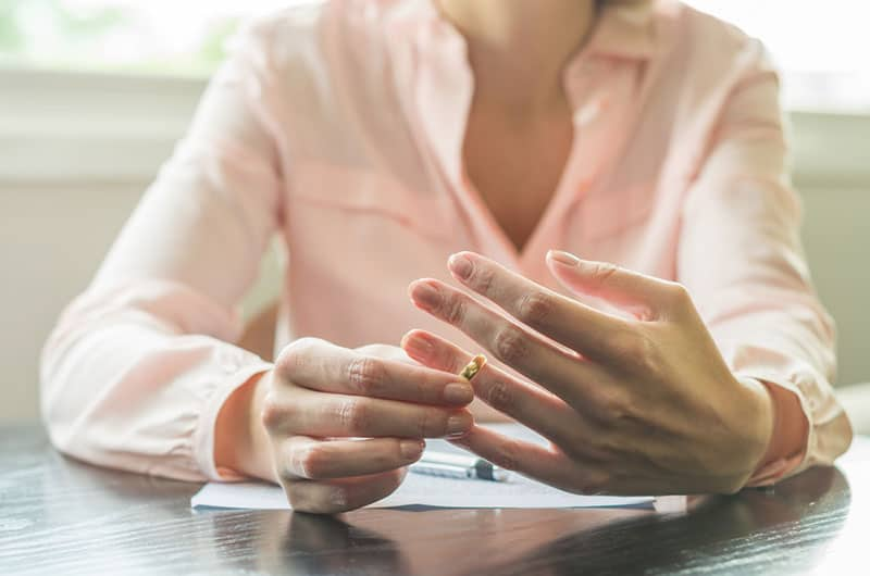Frau nimmt den Ehering ab