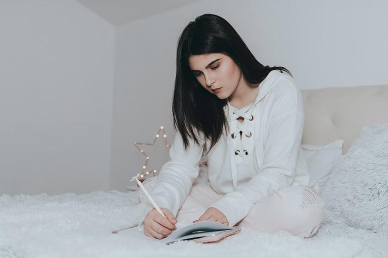 Frau, die in einem Notizbuch schreibt, während sie auf dem Bett sitzt
