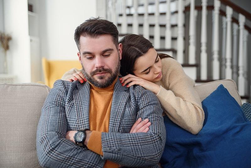 Frau entschuldigt sich bei dem frustrierten Mann und umarmt ihn von hinten