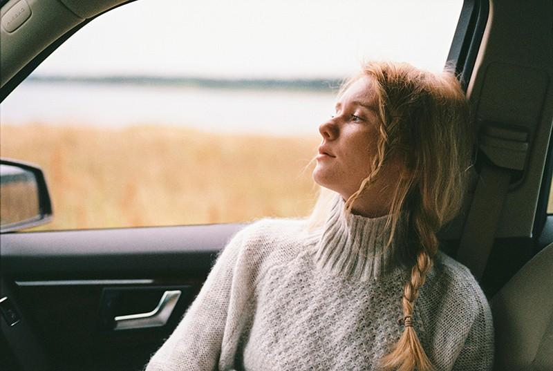 Frau im Pullover sitzt in einem Auto und schaut durch das Fenster