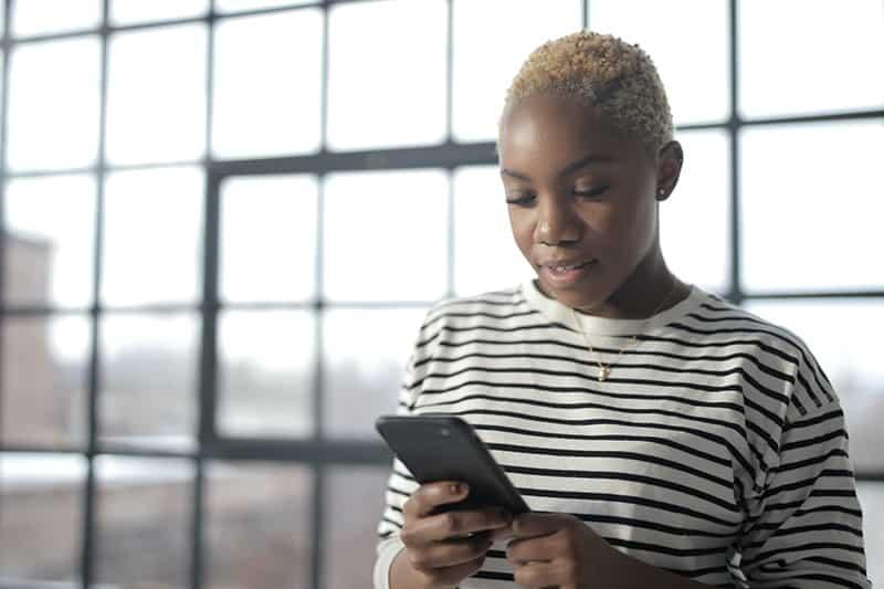 Frau im gestreiften Hemd hält ein Smartphone, während im Raum stehend