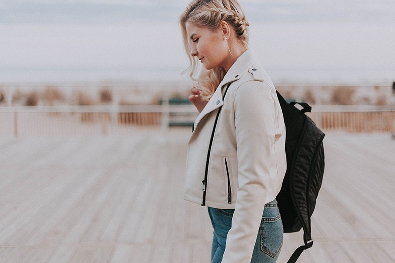 Frau in einer weißen Jacke, die Rucksack hält, der auf der hölzernen Terrasse steht