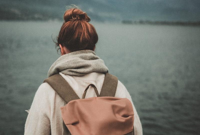 Frau steht in der Nähe ruhiges Gewässer]