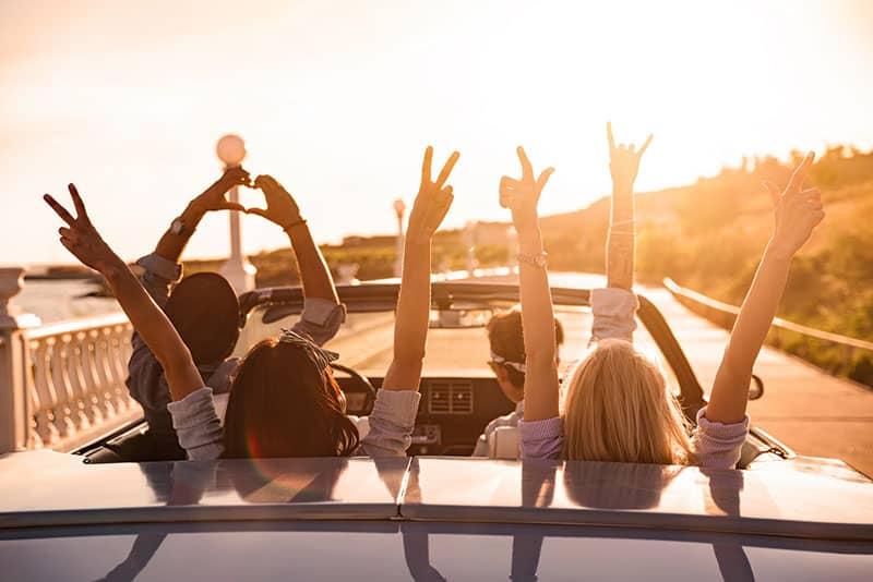 Freunde, die Hände während der Fahrt im Auto heben