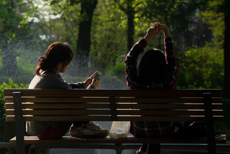 Freunde sitzen auf einer Parkbank und ruhen sich aus