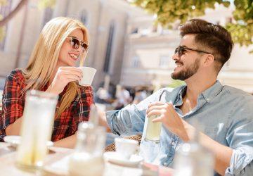 eine lächelnde Frau und ein lächelnder Mann sitzen im Café