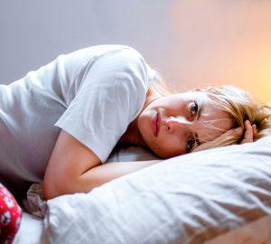 besorgte Frau im Bett liegen