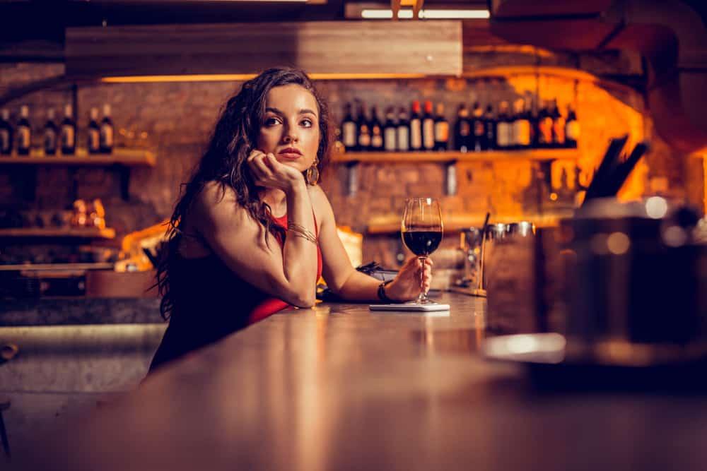 Hinter der Bar sitzt mit einem Glas Wein in der Hand eine nachdenkliche traurige Frau