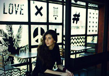 eine nachdenkliche Frau, die alleine im Café sitzt