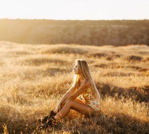Eine hübsche Blondine sitzt auf dem Feld