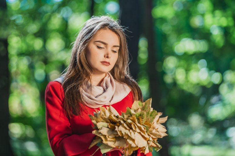 Im Wald steht mit trockenen Blättern in den Händen ein trauriges Mädchen in einem roten Mantel