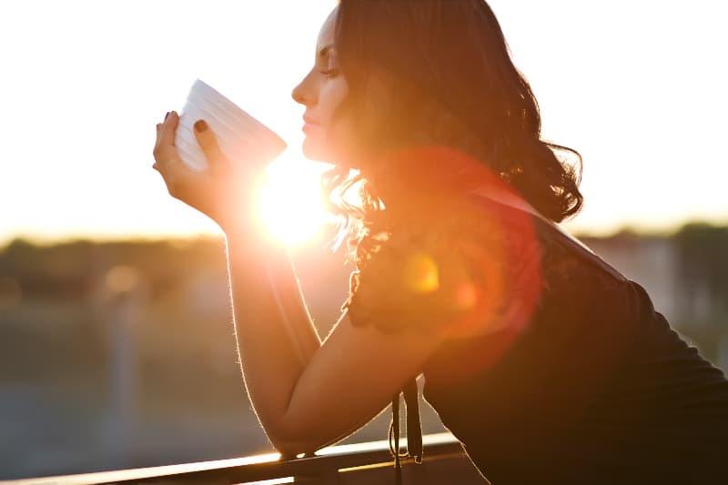 eine Frau, die Kaffee auf dem Balkon bei Sonnenuntergang trinkt