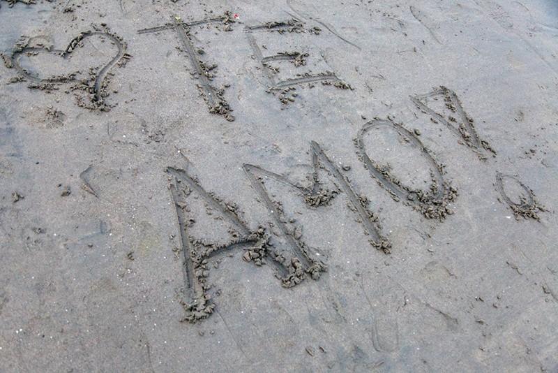 Ich liebe dich in lateinischer Sprache auf den Sand geschrieben