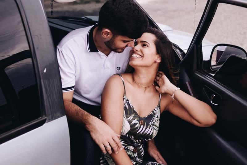 Im Auto sitzt in einer Umarmung ein lächelndes Liebespaar