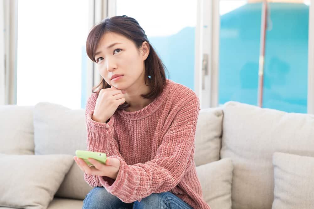 Im Haus auf dem Sofa sitzt eine nachdenkliche traurige Frau mit einem Smartphone in der Hand