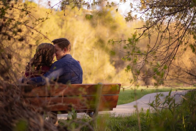 Im Park auf der Bank küsst sich ein liebendes Paar