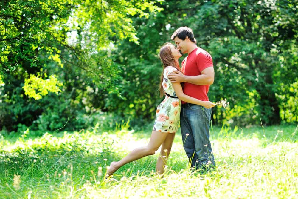 Im Park steht ein liebevolles Paar und sie küssen sich