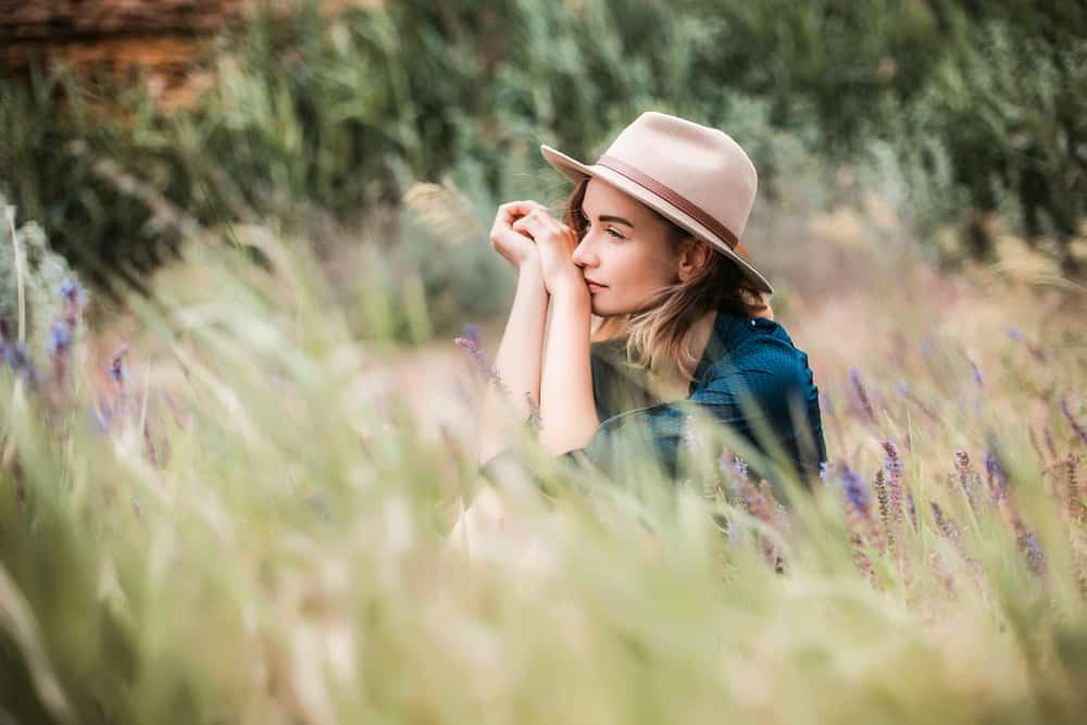Im hohen Gras sitzt ein Mädchen mit Hut und denkt nach