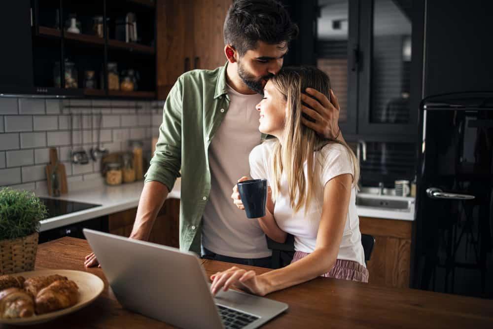 In der Küche am Tisch küsst ein Mann eine Frau auf den Kopf
