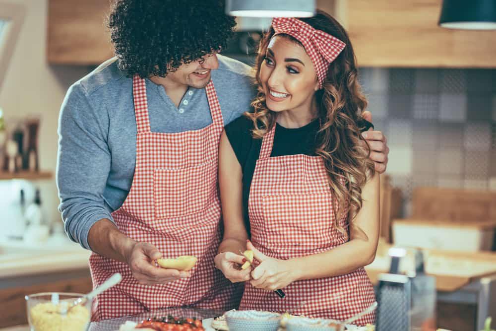 In der Küche bereitet ein lächelndes Paar das Mittagessen vor