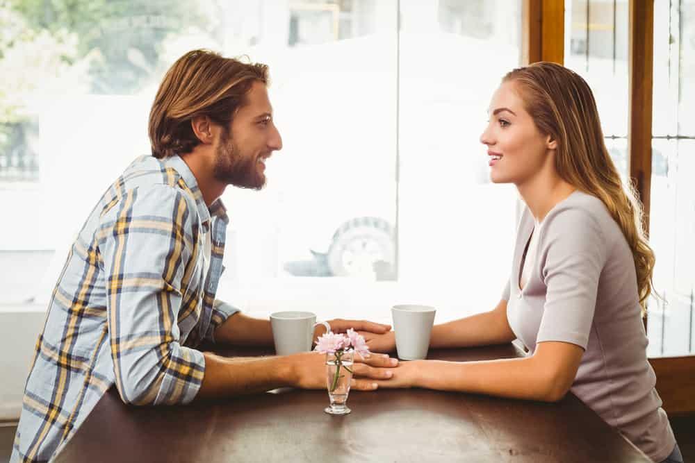 In einem Café an einem Tisch am Fenster sitzen ein lächelnder Mann und eine lächelnde Frau und halten sich an den Händen